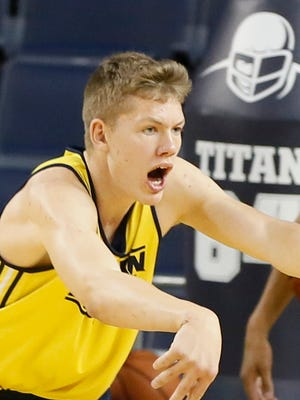 Michigan forward Moritz Wagner passes the ball to start a fast break drill during practice on Thursday.