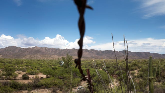 A barbed-wire fence separates the members of the Tohono O'odham Nation in the United States (left) and those in Mexico.