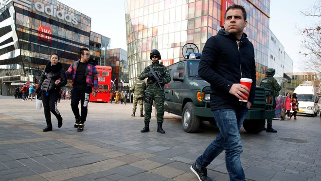 Heavily armed Chinese paramilitary police guard a popular mall in the Sanlitun district of Beijing, China, Dec. 24, 2015.