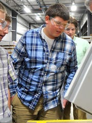 D.C. Everest High School senior Lukas Lindner, center, studies metal fabrication during a tour of Applied Laser Technologies in Weston on Friday, Oct. 9, 2015.