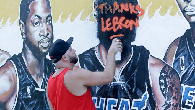 """A man, who did not wish to be identified, spray paints """"Thanks LeBron,"""" over a vandalized mural of the Miami Heat players featuring LeBron James, Friday, July 11, 2014, in Miami. James is returning home to Ohio, reversing the decision he made four years ago that led to two NBA titles in Miami and crushed Cleveland Cavalier fans. """"I just don't want people disrespecting LeBron,"""" the man said, """" He did so much for the city. I've been waiting all day to get off work to do that."""" (AP Photo/Wilfredo Lee)"""
