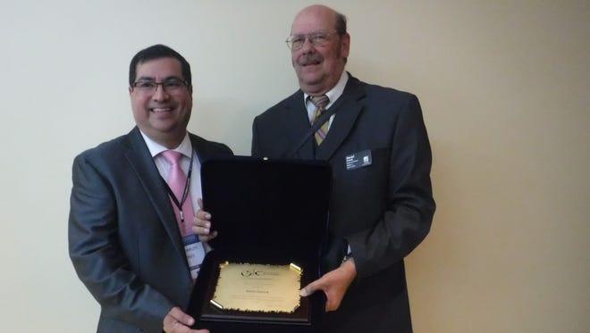 Dan Sniezek is presented the recognition plaque by Jose Carlos Flores Molina, director of the Instituto Para La Calidad at Pontificia Universidad Catolica del Peru.
