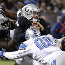 Oakland Raiders quarterback Derek Carr (4) is tackled by Detroit Lions defensive end George Johnson (68) and defensive tackle Andre Fluellen, rear, during the third quarter of an NFL preseason football game in Oakland, Calif., Friday, Aug. 15, 2014.