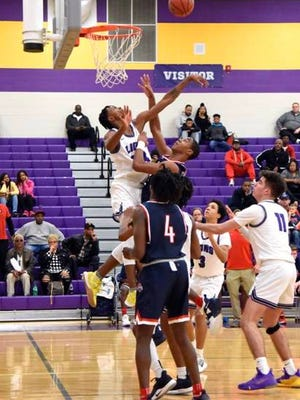 Columbia Central's DQ Mitchell blocks a shot by Oakland's D.D. Anderson during Saturday's Region 4-AAA Tournament quarterfinal. The host Lions saw their season come to an end with a 62-44 loss.
