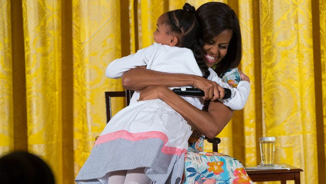 """Anaya Brodie, left, hugs first lady Michelle Obama during the White House's annual """"Take Our Daughters and Sons to Work Day"""" in the East Room on Wednesday, April 22, 2015, in Washington."""