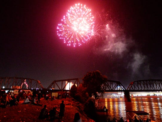 People watch the fireworks on the banks of the Red