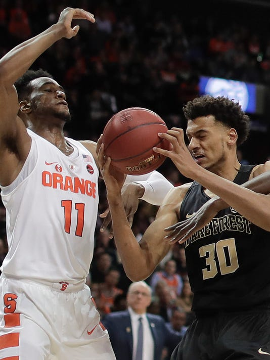 Wake Forest center Olivier Sarr (30) is fouled as he attempts to shoot against Syracuse forward Oshae Brissett (11) during the first half of an NCAA college basketball game in the Atlantic Coast Conference men's tournament Tuesday, March 6, 2018, in New York. (AP Photo/Julie Jacobson)