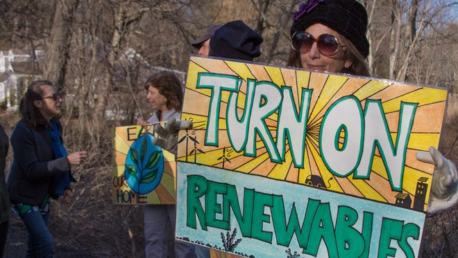 Diane Hawlk holds a sign displaying one of the environmental issues that she is concerned about.  Protesters gatherd at the home of NY Governor Andrew Cuomo in Mount Kisco on Sunday to voice their concerns over the Algonquin Pipeline Project.