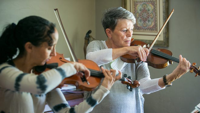 Rosie Schurz (right), founder of Rosie's House music academy, practices violin with instructor Patty Waxman. They'll perform together Monday, April 27.