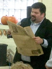 First Latin American Baptist Church Pastor Kevin Casillas reads headlines from a copy of the Detroit Free Press dated September 2, 1904, pulled from a time capsule at the church.ÊThe time capsule was placed in a cornerstone of the Fort Street church building when it was constructed.Ê