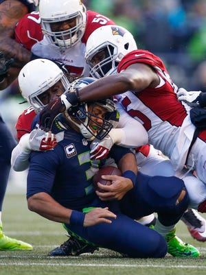 Dec 24, 2016: Arizona Cardinals outside linebacker Chandler Jones (55) and outside linebacker Markus Golden (44) sack Seattle Seahawks quarterback Russell Wilson (3) during the first quarter at CenturyLink Field. Arizona defeated Seattle, 34-31.