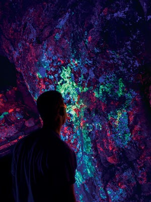 A visitor admires the display of fluorescent minerals in Hull Mine.