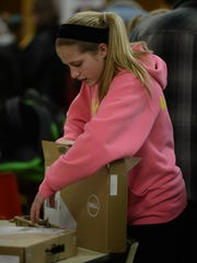 Hagerstown Junior High School student student Makynna Matanich, 12, opens a box containing a Chromebook in January.