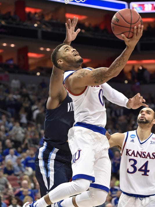 Kansas guard Frank Mason III (0) shoots against Villanova forward Kris Jenkins, left, during the second half of a regional final men's college basketball game in the NCAA Tournament, Saturday, March 26, 2016, in Louisville, Ky. (AP Photo/John Flavell)