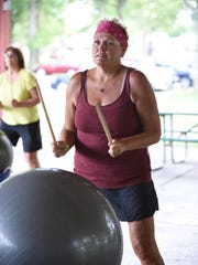 Westland resident Sherri West plays the drums to the music during the cardio-drumming workout.