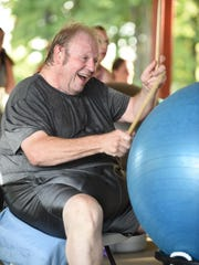 With the enthusiasm of a rock star, Tom Simpson of Dearborn Heights takes part in the cardio-drumming workout Tuesday in Garden City.