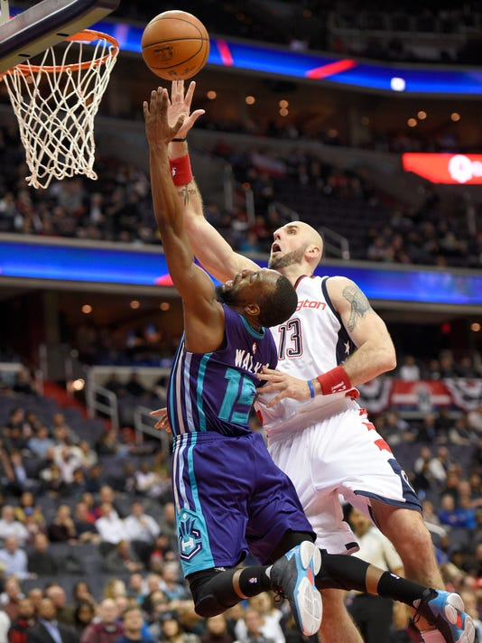 Charlotte Hornets guard Kemba Walker (15) goes to the basket against Washington Wizards center Marcin Gortat, of Poland, (13) during the first half of an NBA basketball game, Wednesday, Dec. 14, 2016, in Washington. (AP Photo/Nick Wass)
