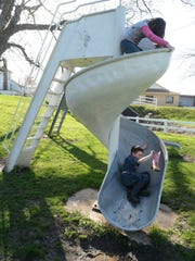 Grace Callahan, 7, top, and Morgan Hoos, 6, play on a slide at Maplewood Park in Centerville.