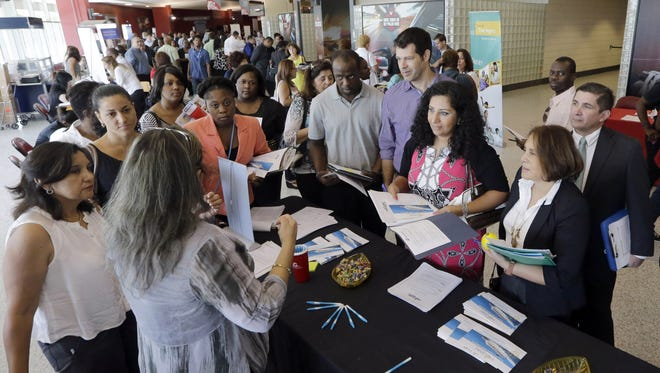 In this June 10, 2015, photo, job seekers get information at a job fair in Sunrise, Fla. The Labor Department releases weekly jobless claims on Thursday, Aug. 20, 2015.