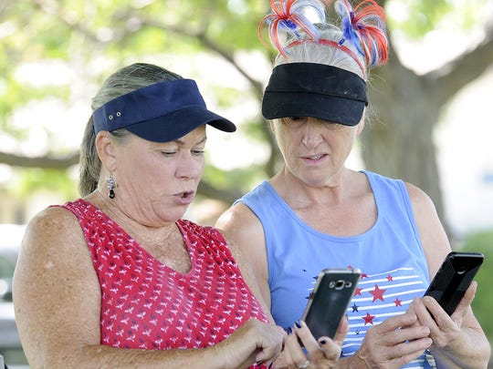 Donna Long (left) of Roseville and Karen Jones of Placerville check their phones while hanging out in the shade.