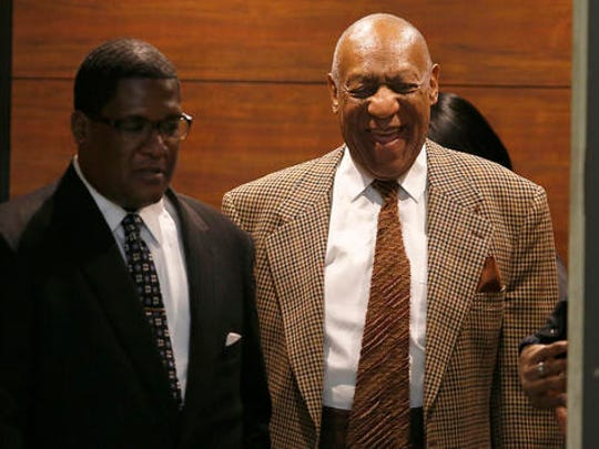 Bill Cosby, right, laughs as he exits the elevator