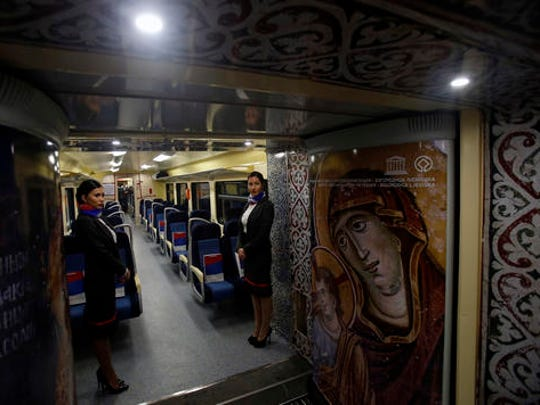 Train hostesses stand in a train carriage decorated with iconic religious figures as it departs from Belgrade to Mitrovica, Kosovo at Belgrade's railway station, Serbia, Saturday, Jan. 14, 2017. Serbia has launched a railway link to Serb-dominated northern Kosovo despite protests from authorities in Pristina who described the move as a provocation and an aggressive violation of Kosovo's sovereignty.