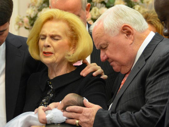 In this 2012 provided by a former member of the church, Word of Faith Fellowship leader Jane Whaley, center left, holds Jeffrey Cooper's infant daughter, accompanied by her husband, Sam, center right, and others during a ceremony in the church's compound in Spindale, N.C. At least a half-dozen times over two decades, authorities investigated reports that members of a secretive evangelical church were being beaten. And every time, according to former congregants, the orders came down from church leaders: They must lie to protect the sect.
