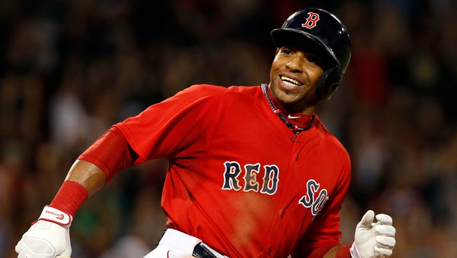 Boston Red Sox outfielder Yoenis Cespedes smiles at teammates charging out of the dugout after hitting the winning RBI single against the Toronto Blue Jays on Sept. 5, 2014.