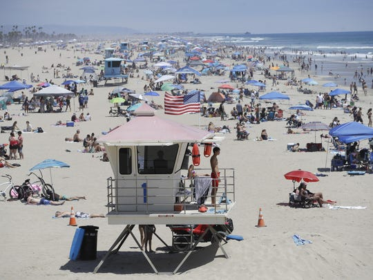 A lifeguard keeps watch over a packed beach Saturday in Huntington Beach, Calif.