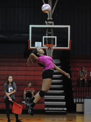 Evangel's Giselle Rogers serves against Mansfield on Tuesday night.