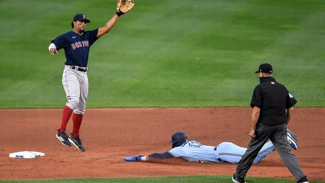 Boston Red Sox shortstop Xander Bogaerts, left, reaches for the throw as Toronto Blue Jays' Lourdes Gurriel Jr., center, slides into second with a stolen base during the second inning of a baseball game in Buffalo, N.Y., Wednesday, Aug. 26, 2020.