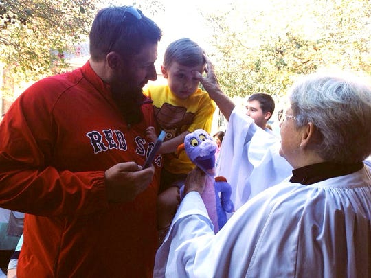 After blessing Figgy the Dinosaur (center), the Rev. Ella Breckenridge (right) blesses Reese Welch, 2, who is held by his father Scott Welch, at a blessing of the animals Friday at St. James Episcopal Day School.
