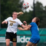 Vermont's Dana Buckhorn (20) kicks the ball between several Central Connecticut defenders during the women's soccer game last season at Virtue Field.