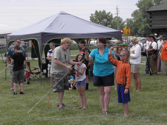 Children learn to use an 'atlatl,' a historical spear-throwing