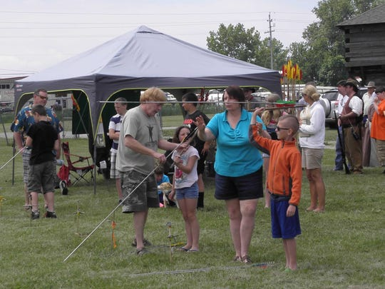 Children learn to use an 'atlatl,' a historical spear-throwing tool, during the Pioneer and Primitive Arts Festival at Fort Firelands RV Resort in Marblehead.