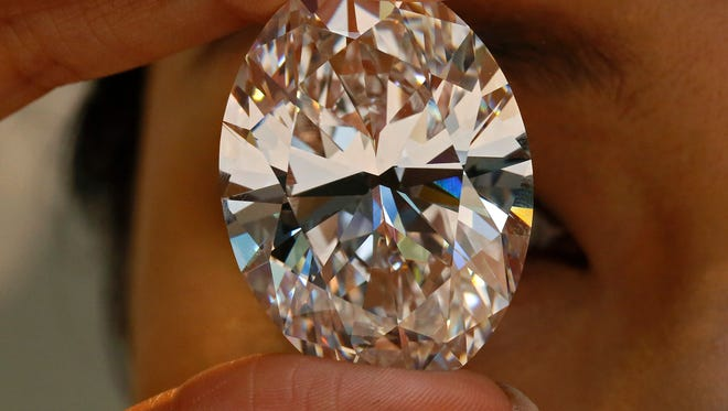 A 118.28-carat white diamond is displayed at a press preview at Sotheby's auction house, Thursday, Sept. 19, 2013 in Hong Kong. The oval stone will be auctioned off in Hong Kong on Oct. 7 and has a pre-sale estimate of US$28 million to $35 million. The current record for any white diamond is US$26.7 million. (AP Photo/Vincent Yu) ORG XMIT: XVY101