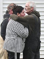 Homeowners Robert and Tammy Bletz embrace as they watch their home at 16 Vanderbilt Road burn Friday afternoon as local firefighters from Washington and Troy Townships worked to extinguish the blaze.