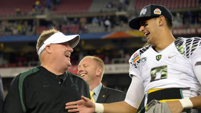 Oregon Ducks coach Chip Kelly (left) and quarterback Marcus Mariota (8) celebrate after the 2013 Fiesta Bowl against the Kansas State Wildcats at University of Phoenix Stadium.