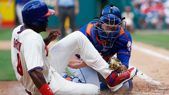 Philadelphia's Domonic Brown, left, is tagged out at home plate by the Mets' Anthony Recker after trying to score on a single by Ben Revere in the seventh inning on Monday, in Philadelphia.