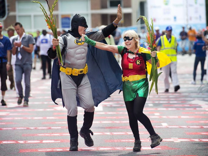 Participants wearing costumes cross the finish line