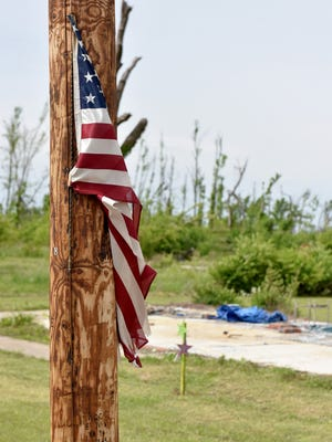 An American flag hangs from a utility pole near the slab of a home on Eiland Ave. destroyed by last year's tornado.