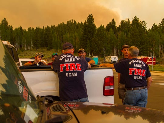 Members of the Panguitch Lake Fire Department wait in a LDS Church parking lot with the Brian Head fire burning in the background on Saturday, June 24, 2017.