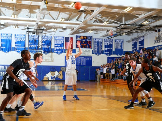 Millburn senior Ross Gang (33) shoots a free throw for his 1,000th career point.