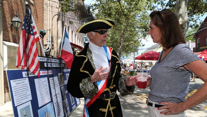 Richard Esnard, with the Piermont Historical Society, gives a history lesson to Deb Deck during the 7th annual Bastille Day celebration in Piermont, July 16, 2016.