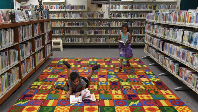 Siblings Aaliyah Garcia, 7, and Alyssa Garcia, 6, stop to read at the Duncan/Traner Library on Tuesday afternoon.