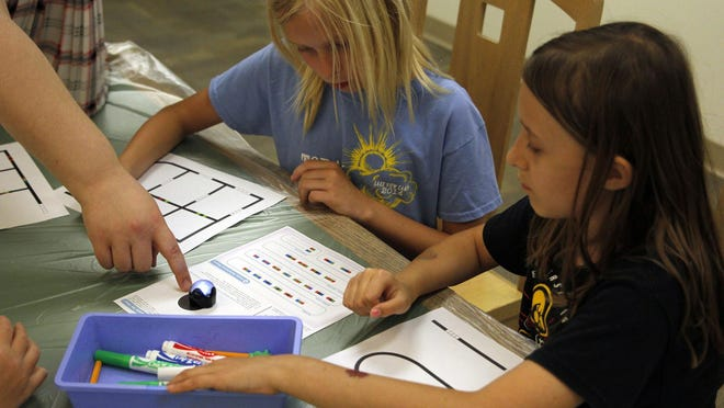 Kirsten Milczski and Madison Oppelt learn how to move their robot around on the black lines. Color patterns interrupting the black lines gave the robot its next step.