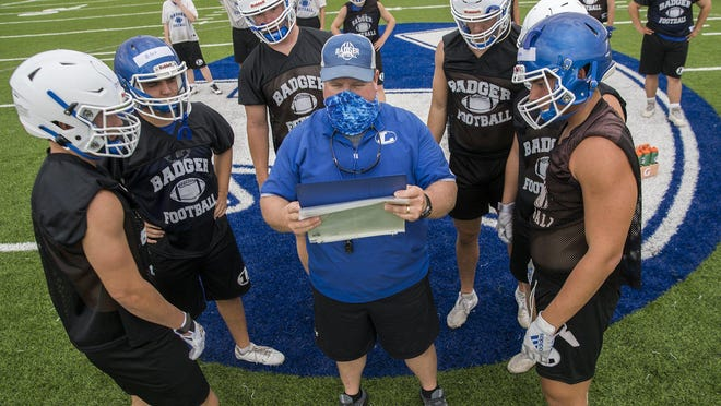 Lampasas linebackers coach David Brister coaches up his players as they start their practice Monday, the first day Class 4A and smaller schools were allowed to begin fall football practices.