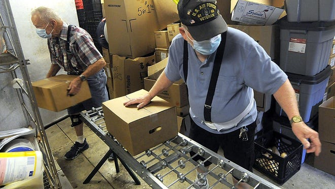 Ernie Cline, left, and Jim Belcher unload boxes of food into a walk-in refrigerator for the Hillsdale Cares ministry at Jeromesville Christian Church, in an Ashland County village roughly halfway between Cleveland and Columbus.
