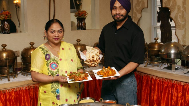 Sarabjit Kaur and husband, Kulwant Singh, with two popular dishes at their restaurant, Divine Curry in Hillsborough.