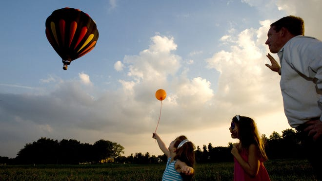 Libby and Lexie Parkins watch a hot-air balloon with their dad, Blake Parkins. The Parkins family had just come from dinner, where the girls received balloons, when they saw the hot-air balloon and decided to pull over to watch it land.